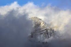 Montagnes de neige au coucher du soleil avec le brouillard Photo stock