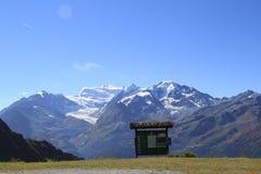 Montagnes de neige bas nuages et le ciel bleu Photographie stock libre de droits