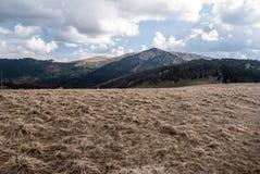 Montagnes de ressort avec le pré de montagne, collines avec des champs de neige et ciel bleu avec des nuages Image stock