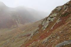 Montagnes en automne avec l'herbe brune et rougeâtre sous le ciel nuageux photos libres de droits