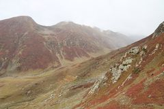Montagnes en automne avec l'herbe brune et rougeâtre sous le ciel nuageux image libre de droits