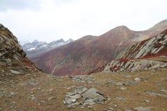 Montagnes en automne avec l'herbe brune et rougeâtre sous le ciel nuageux photographie stock libre de droits