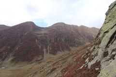 Montagnes en automne avec l'herbe brune et rougeâtre sous le ciel nuageux images libres de droits