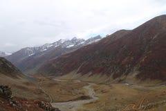Montagnes en automne avec l'herbe brune et rougeâtre sous le ciel nuageux photographie stock