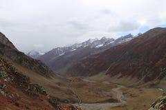 Montagnes en automne avec l'herbe brune et rougeâtre sous le ciel nuageux photos stock