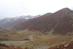Montagnes en automne avec l'herbe brune et rougeâtre sous le ciel nuageux photo stock