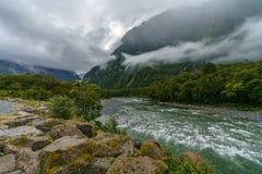 Montagnes en bas nuages accrochants, rivière de cleddau, Milford Sound, Nouvelle Zélande 11 photographie stock