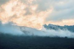 Montagnes en nuages au coucher du soleil Photos stock