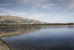 Montagnes et arbres reflétés au-dessus de l'eau d'un lac photo stock