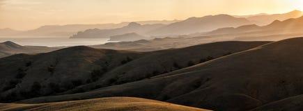 Montagnes et collines allumées par le soleil Photographie stock