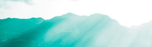Montagnes et faisceaux lumineux du soleil lumineux Photographie stock