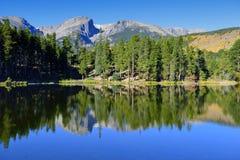Montagnes et lac alpin avec la réflexion en automne Photographie stock
