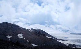 Montagnes et nuages Snow-covered photographie stock