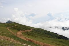 Montagnes et prés verts dans les nuages images libres de droits