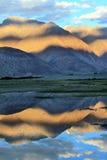 Montagnes et réflexion dans l'eau. Coucher du soleil Photos stock