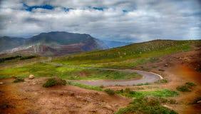 Montagnes, herbe verte, moulins à vent et un ciel nuageux Photo libre de droits