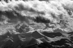 Montagnes noires et blanches de soirée et ciel nuageux Photographie stock