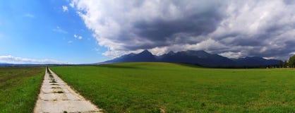 Montagnes nuageuses de jour ensoleillé Photographie stock libre de droits