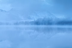 Montagnes reflétées dans le lac en brouillard dense Photographie stock