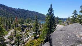 Montagnes rocheuses, forêt et lac dans l'avant avec le ciel bleu clair Photo stock