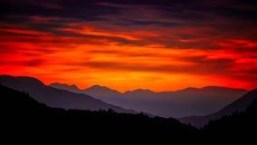 Montagnes sous un ciel fiewry Image libre de droits