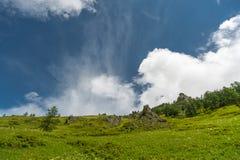 Montagnes vertes avec les nuages colorés et le ciel bleu Images libres de droits