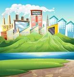 Montagnes vertes près de la rivière et des bâtiments Photo stock