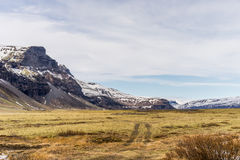 Montain range and plains with field road in view Royalty Free Stock Images