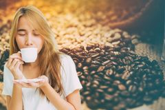 Montaje de consumición adolescente del café de la muchacha con el café del grano de café Imagen de archivo