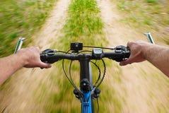 Montaje de la velocidad biking en el camino de tierra Imagen de archivo