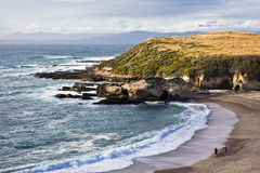 Montana de Oro. Rugged point in Montano de Oro State Park is illuminated by sunlight on a mostly cloudy day south of Morro Bay, California Royalty Free Stock Image