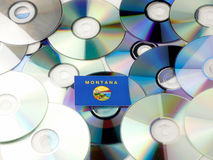 Montana flag on top of CD and DVD pile isolated on white Stock Photography