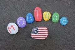 Montana, los Estados Unidos de América, recuerdo con las piedras multicoloras sobre la arena volcánica negra Imagenes de archivo