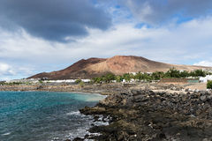 Montana Roch as seen from PLaya Blanca. The Red Mountain as it is also called by visitors of the island. Between the volcano and the sea are a string of resorts royalty free stock photos