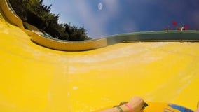 Montando abajo en el tobogán acuático en el cuenco o la balsa inflable, primera opinión de la persona almacen de metraje de vídeo