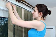 Montando los obturadores, los listones de las persianas de la tela del gancho de la muchacha, instalan persianas Imagenes de archivo