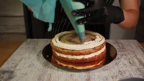Montando o bolo da porca-banana, aplicando o creme da manteiga, folha de prova que enche, o processo inteiro vídeos de arquivo