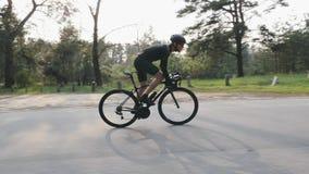 Montando um lado da bicicleta siga a vista Homem farpado no equipamento preto na bicicleta no parque Fora do pedaling da sela filme