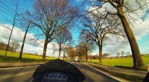 Montando um velomotor em uma estrada entre os campos Fotos de Stock