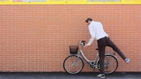Montando uma bicicleta e montando afastado video estoque