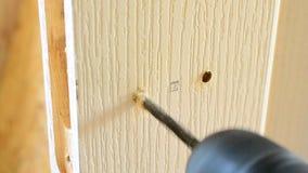 Montando una cerradura de puerta - agujeros de perforación en un blanco metrajes