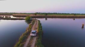 Montanha aérea de Photography O carro move-se ao longo de uma estrada estreita entre os lagos Lagoa de peixes Manhã do verão Ivan filme