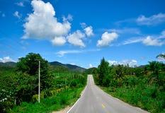 montanha, as nuvens do céu e a estrada Imagens de Stock