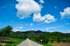 montanha, as nuvens do céu e a estrada Imagem de Stock