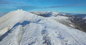 A montanha coberta com a neve O zangão voa para trás, filmando as montanhas vídeos de arquivo