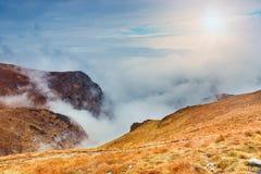 Montanha com névoa abaixo dos picos e das nuvens acima deles fotos de stock royalty free