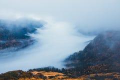 Montanha com névoa abaixo dos picos e das nuvens acima deles fotos de stock