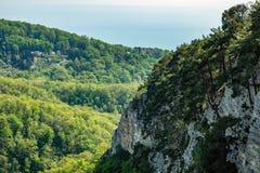 Montanha com uma inclina??o rochosa ?ngreme e vale com a floresta verde grossa abaixo foto de stock royalty free