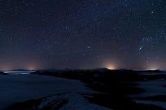 Montanha contra a obscuridade - o céu azul com protagoniza na noite imagens de stock