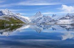 A montanha da neve com reflexão no céu azul do lago e do espaço livre dentro imagem de stock